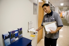 Photo of Penn staff member placing mail into mail slot