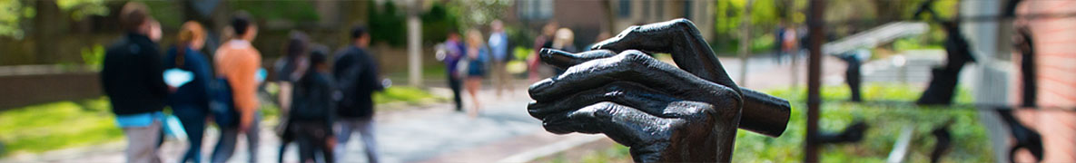 Banner Image - students walking on campus, hand of statue holding penn in foreground